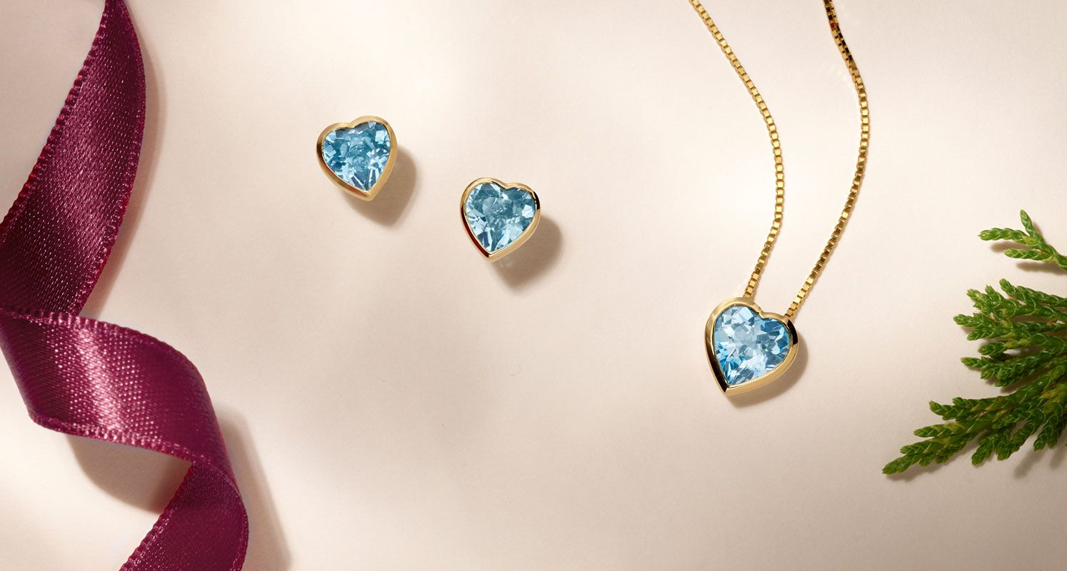 A matching set of blue heart shaped gemstone earrings and pendant