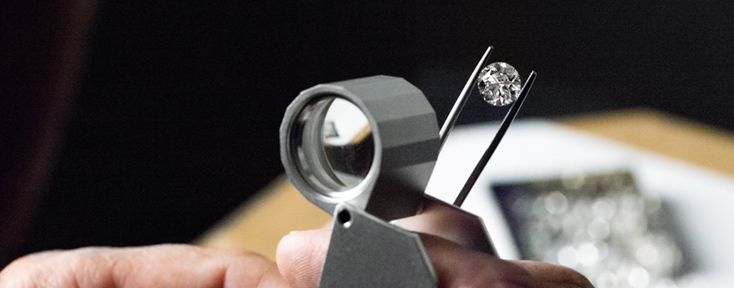 Person Using Magnifier To Check Clarity of A Round Diamond
