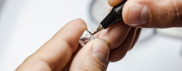 Close Up of Hands Holding Loose Diamond and Tool