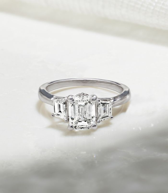 A Cathedral Engagement Ring Sitting on Flat Surface