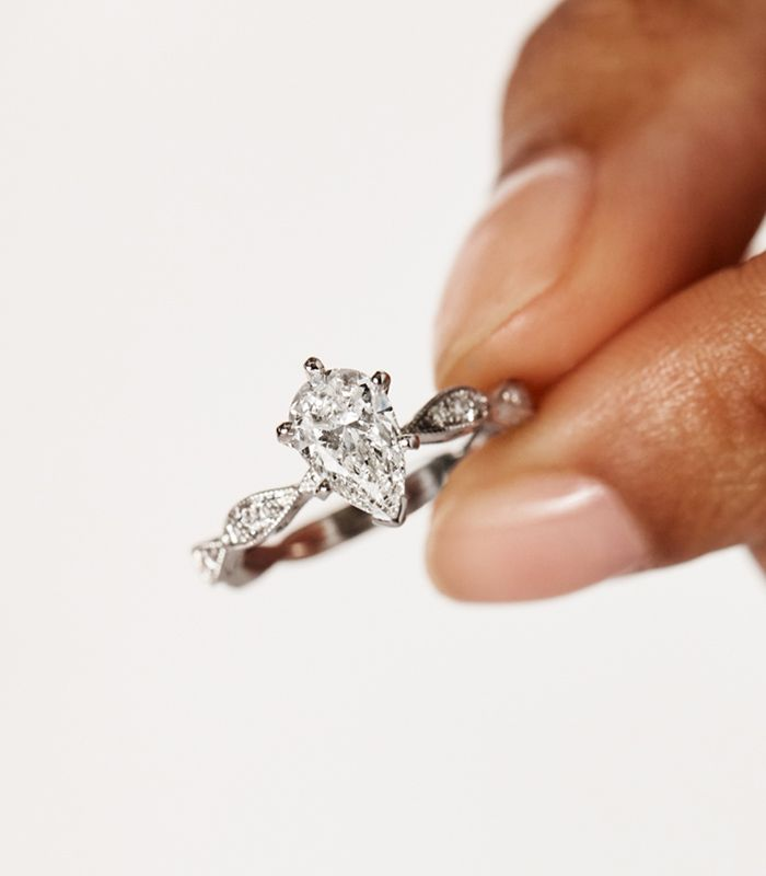 Woman Holding A Pave Engagement Ring Between Fingers