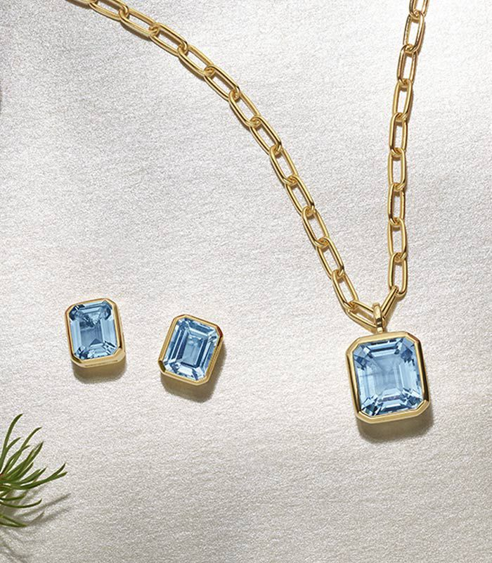 Mobile image of a pair of blue topaz earrings and matching pendant