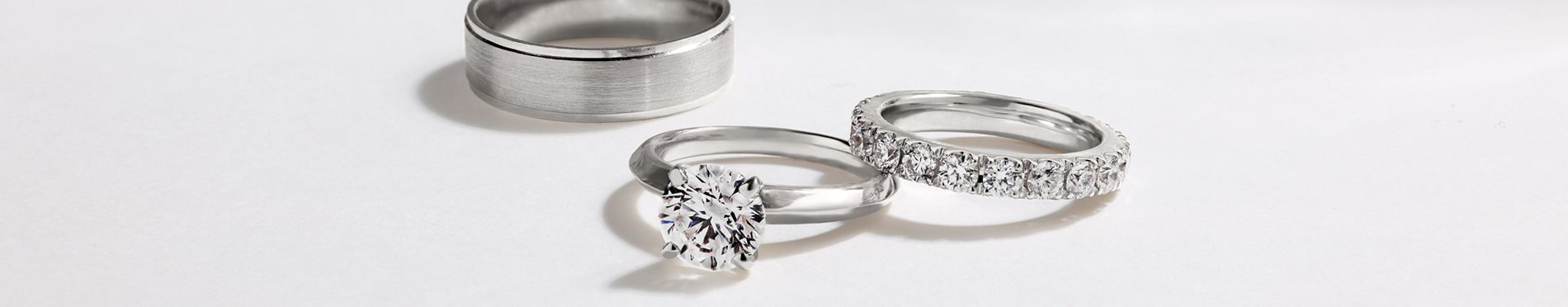 Desktop Image of a Men's Wedding Band, a Diamond Engagement Ring, and a Diamond Wedding Band