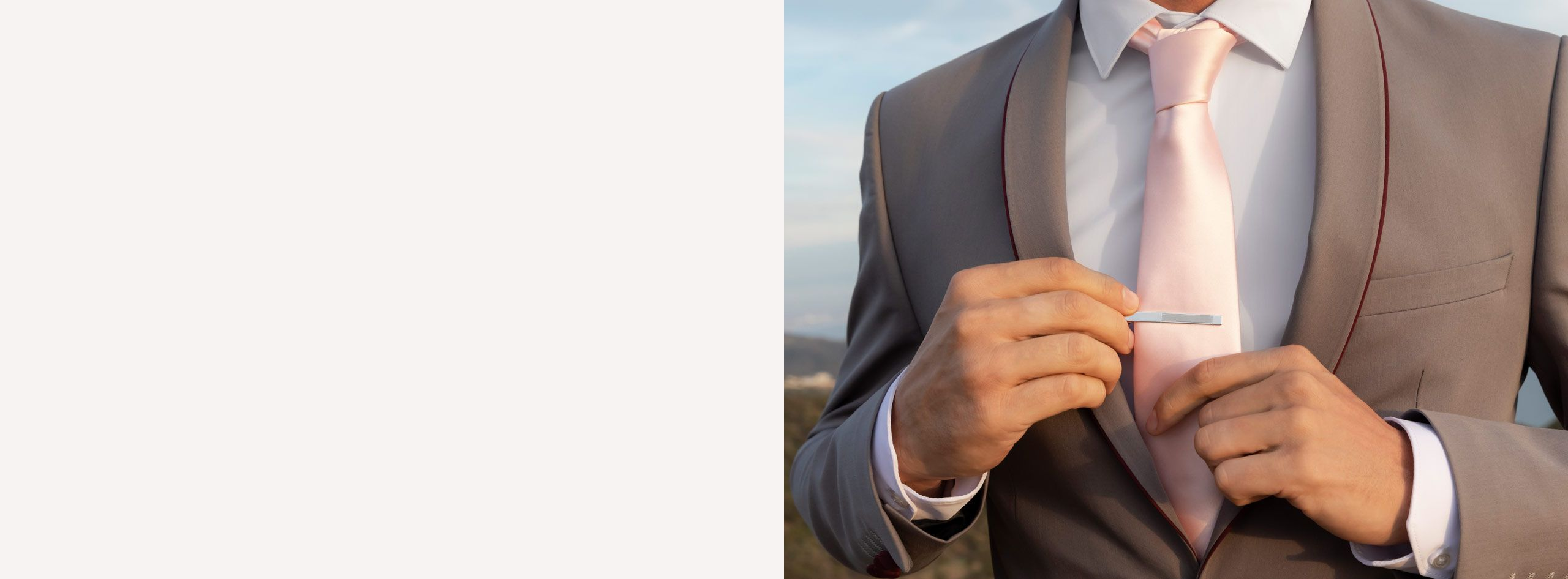 Close Up of Man Putting Silver Tie Clip on Tie