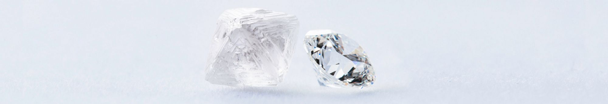 Desktop image of a rough diamond and a cut round diamond