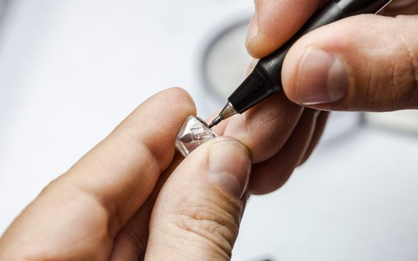 Person Using Tool To Cut Loose Diamond