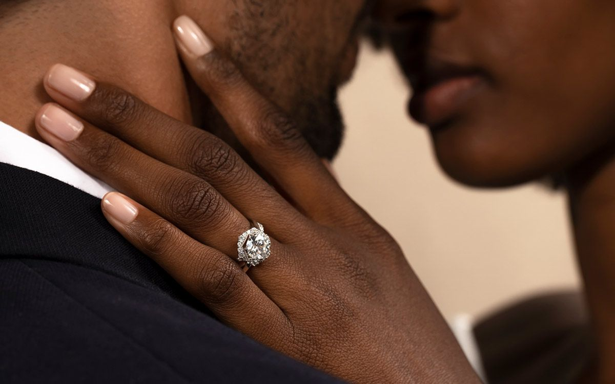 Mobile Image of Couple Embracing while showing off her engagement ring