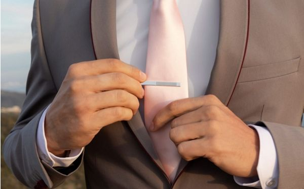 Mobile image of Close Up of Man Putting Silver Tie Clip on Tie