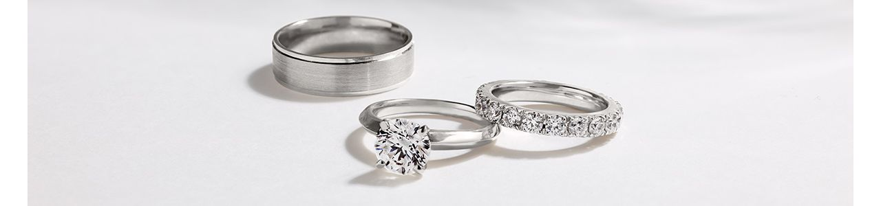 Mobile Image of a Men's Wedding Band, a Diamond Engagement Ring, and a Diamond Wedding Band