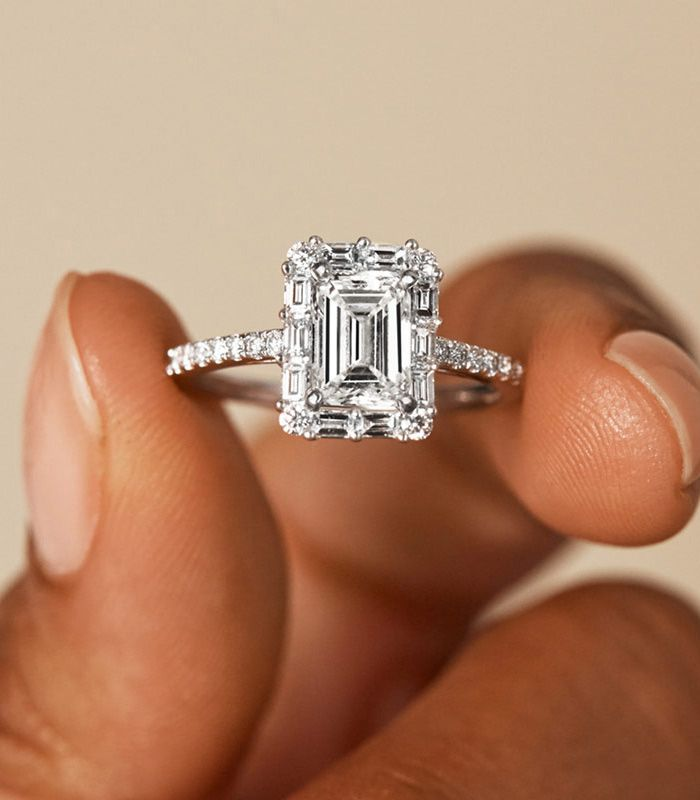 Woman Holding Classic Engagement Ring Between Fingers